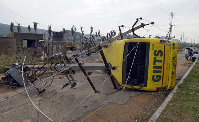 Power lines and a passenger bus are seen after being damaged by strong winds caused by Cyclone Hudhud in Visakhapatnam October 13. (Reuters)